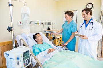 Patient Looking At Medical Team In Hospital Room