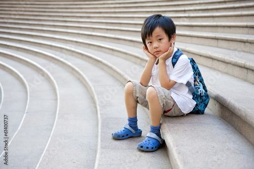 Cute schoolboy sitting on the stairs