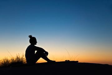 Silhouette de femme assise, soleil couchant
