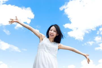 青空を背に手を広げる女性