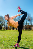 Young attractive woman doing stretching exercise outdoors