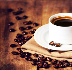 Cup of coffee with coffee beans on wooden table on brown backgro