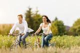Fototapety Junges Paar fahren Fahrrad im Sommer