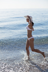 Young woman running along the beach.