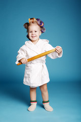young housewife with rolling pin on blue background