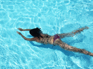 Young woman under water in the swimming pool.