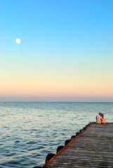 Man and woman on a pier in the moonlight