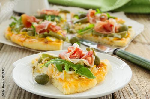 Pizza with arugula and prosciutto.