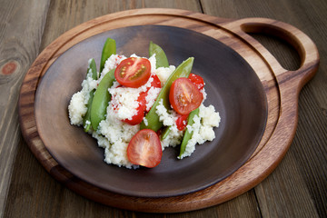 Couscous with peas and cherry tomatoes in a ceramic plate