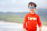 Cute little boy in blue swim goggles on beach