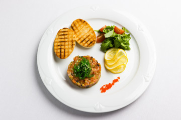 Fish tartare with vegetables and crackers