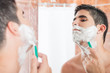 Shirtless hispanic man shaving in front of a mirror