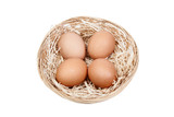Wicker basket with four eggs on straw