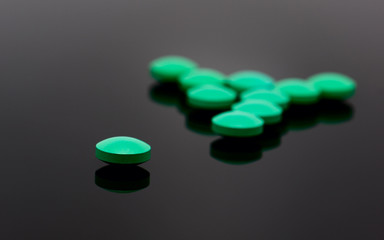 green pills on black background