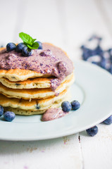 Blueberry pancakes on white wooden background