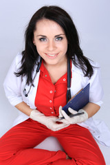 A sexy smiling  woman doctor in medical white and red uniform si