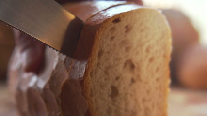 Hand cutting fresh white bread, super slow motion,  at 240fps