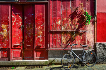 Red wooden wall with door and bicycle
