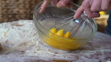 Mixing egg with whisk in glass bowl