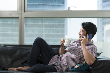 Asian man at home talking on phone