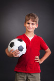 Cute boy is holding a football ball. Soccer ball