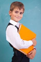 Ñute schoolboy is holding an orange book
