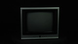 Old TV rotates on a black background loop