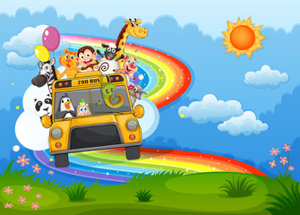 A zoo bus at the hilltop with a rainbow in the sky
