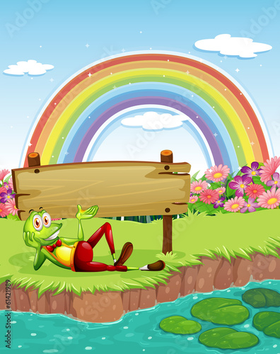 A frog at the pond with a wooden board and a rainbow in the sky