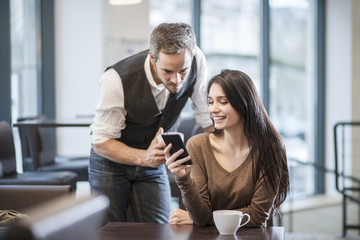 two young people watching a smartphone in a cafe