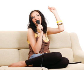 Portrait of a girl with a microphone sitting on the sofa