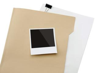 Blank instant print clipped to manila folder.
