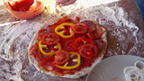 Spicy pepper falling on tasty pizza, super slow motion,