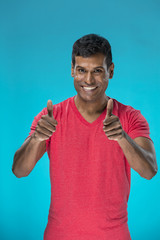 Cheerful Indian man celebrating with his thumbs up.