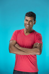 Indian man standing against blue background.