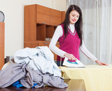 brunette woman ironing  in home