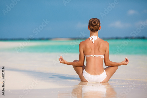 Portrait of a young woman doing yoga on a tropical beach