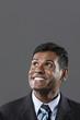 Happy Indian businessman looking upwards.