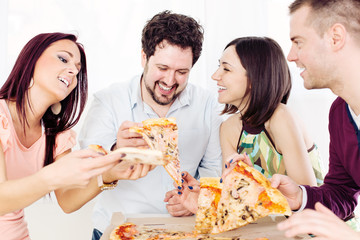 Group of happy friends sitting and eating pizza.