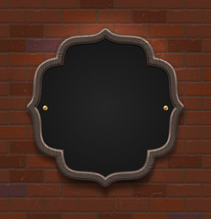 Chalkboard in wooden frame on vintage brick wall
