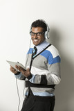 Indian man with tablet PC listen to music.