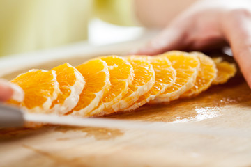 Female hands Cutting Orange in a kitchen.