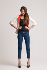 The beautiful young girl in a fashionable jacket. Studio portrai