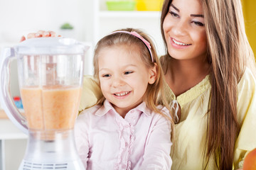 Young woman and cute little girl preparing healthy drink.