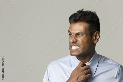 Indian business man adjusting his tie.