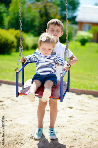 Little brother and sister swinging in summer park