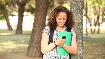 Beautiful Young Student with Mobile Phone at Park