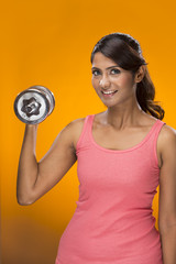 Sporty Indian woman exercising with weights.
