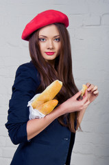 Beautiful young Frenchwoman holding a baguette
