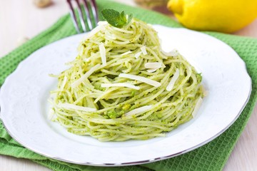 Italian green pasta spaghetti with pesto green peas, mint